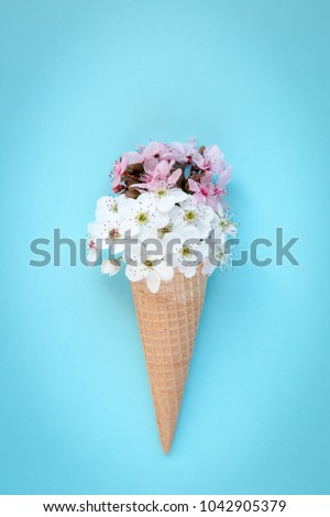 Fashion food set of Ice cream cone with white and pink flowers on top over a blue background, minimalistic design.  #1042905379