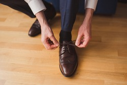 Fashion for men. Close-up of a man tie the shoelaces of his brown leather shoes