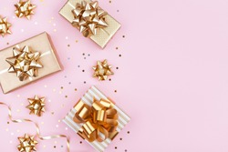 Fashion gifts or presents boxes with golden bows and star confetti on pink pastel table top view. Flat lay composition for birthday, christmas or wedding.
