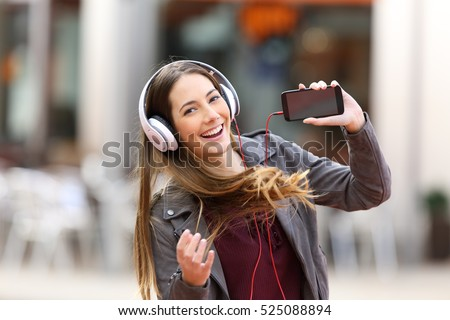 Fashion girl dancing and listening music showing a blank screen of a smart phone and looking at you in the street #525088894