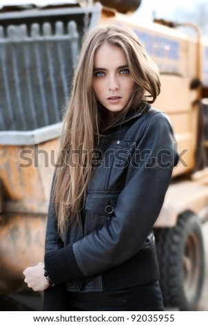 Fashion girl in a jacket next to the construction