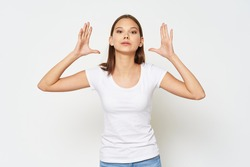 Fashion girl in a white t-shirt gesticulating with hands on an isolated background
