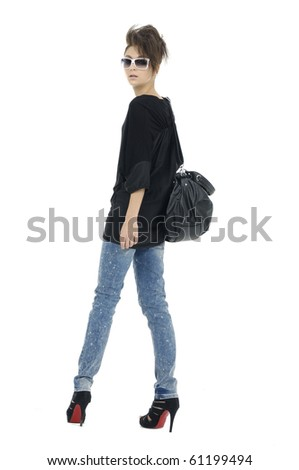 Fashion girl in sunglasses and jeans show in studio back