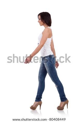 Fashion girl wearing shirt and jeans walking in studio