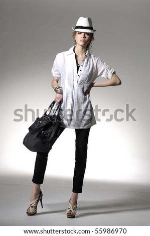 Fashion girl with bag posing in light background