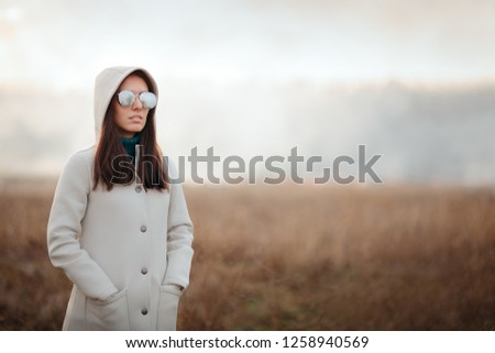 Fashion Girl with Cool Sunglasses Standing on a Field. Fashionable woman posing in outdoor portrait  #1258940569