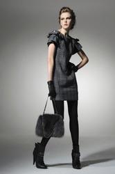 Fashion girl with handbag posing in light background