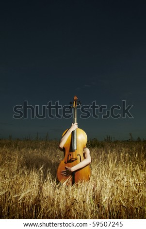 Fashion girl with violoncello in field photo shooting on nature