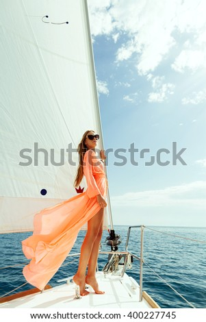 fashion girl yachting in sea with sarong and blue sky sunlight #400227745