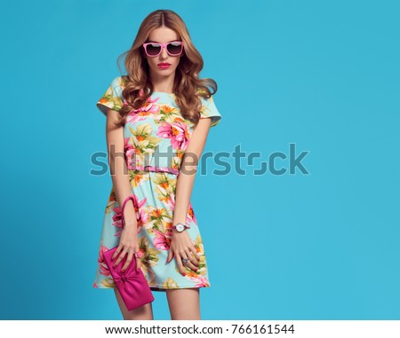Fashion. Glamour Sexy Blond Model. Young woman in Floral Dress. Trendy, Stylish wavy Hairstyle, fashionable Sunglasses, Pink Clutch. Playful Summer Girl