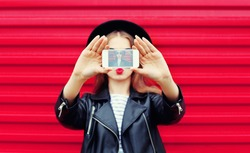 Fashion glamour woman makes self portrait on smartphone blowing lips over city pink background