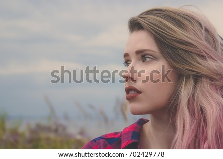 Fashion half-face portrait of young hipster women with colorful hair. Summer concept, sandy beach, bright sky and sea. Tourism, travel, holidays. Washed effect