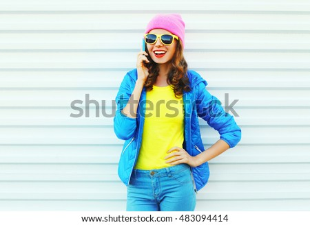 Fashion happy cool smiling girl talking on smartphone in colorful clothes over white background wearing pink hat yellow sunglasses and blue jacket
