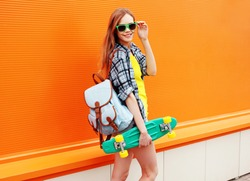 Fashion happy smiling hipster cool girl in sunglasses with skateboard and backpack having fun against the colorful orange wall