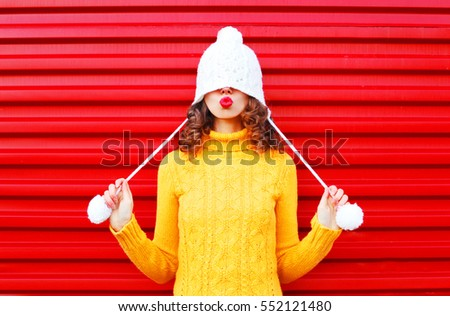 Stock Photo Fashion happy woman blowing red lips makes air kiss wearing colorful knitted hat, yellow sweater over red background