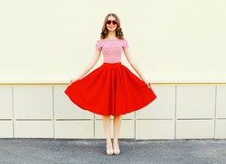 Fashion happy young smiling woman shows a red skirt over white city background