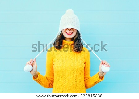 Fashion happy young woman in knitted hat and sweater having fun over colorful blue background #525815638