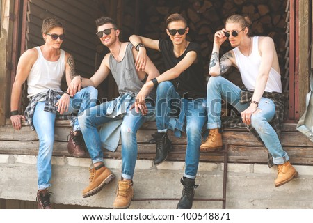 fashion hipster guys sitting near the wall, dressed in jeans and a plaid shirt, sunglasses, Vogue Style