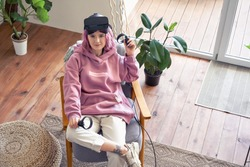 Fashion hipster teen girl pink hair wear vr glasses headset hold controller sit in chair at home look at camera. Digital innovation video gaming, virtual reality 3D 360 apps. Top view above portrait.