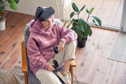 Fashion hipster teen girl pink hair wear vr glasses headset hold controller sit in chair relax at home look away. Digital innovation video gaming, virtual reality 3D 360 apps. Top view from above.