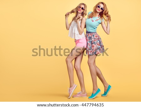 Fashion Hipster woman in Stylish Summer fashion Outfit Having fun. Hipster sisters friends crazy cheeky. Girl in Hipster Fashion sunglasses,Glamour fashion hairstyle posing on yellow. Unusual Creative