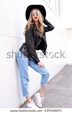 Fashion hipster woman posing outdoor. Black hat, leather jacket, blond curly hair, bright red lips, sunglasses.Trendy fashion style #439568695