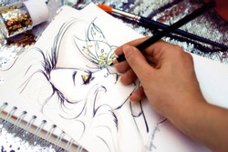 Fashion illustrator drawing a sketch with glitter