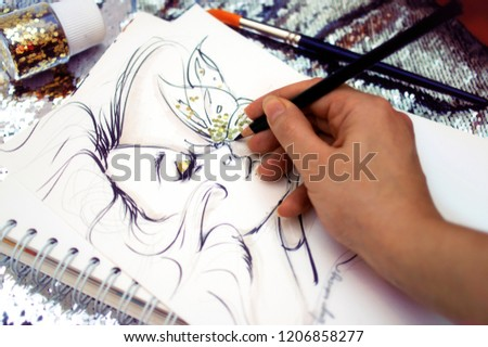 Fashion illustrator drawing a sketch with glitter #1206858277