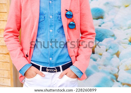 Fashion image of stylish man posing at bright peach jacket, denim shier and white pants at colored background, holding stylish hipster mirrored sunglasses, classic dandy style.