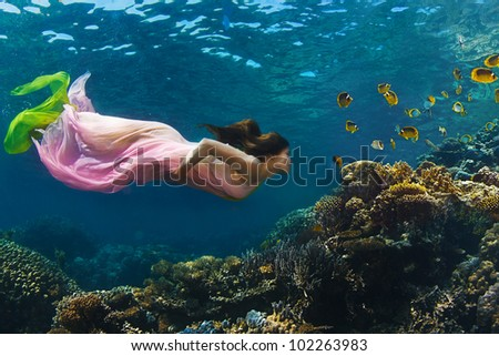 Fashion in tropical paradise. Beautiful model underwater watching colorful coral reef full of yellow fish