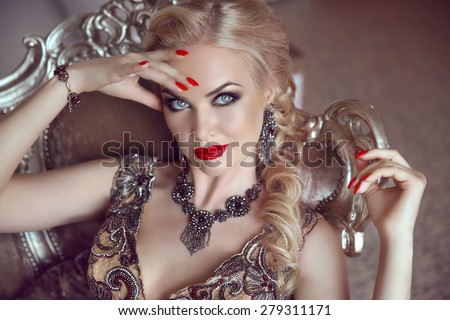 Fashion indoor portrait of beautiful sensual blond woman with makeup in luxurious dress with bijou, posing on modern armchair with sliver frames.