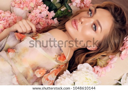 fashion interior photo of beautiful sensual girl with blond curly hair in elegant clothes, posing with flowers