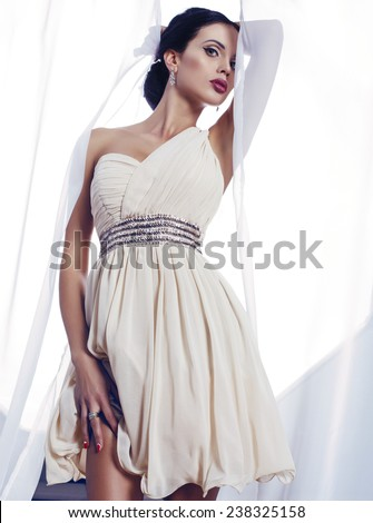 fashion interior photo of beautiful sensual woman with dark hair wearing elegant cocktail dress