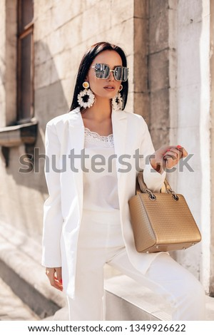fashion interior photo of beautiful woman with dark hair in elegant white suit and coat, with accessories posing on the spring street