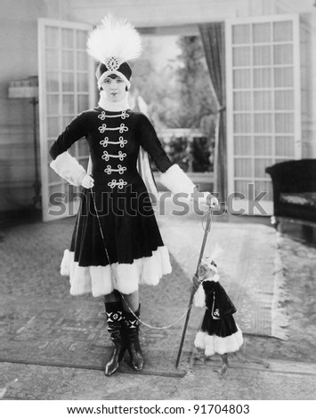 Fashion is not a monkey on her back, as a young woman wears the same Kosak outfit as her pet - stock photo