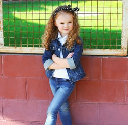 Fashion kid concept - stylish little girl child wearing a jeans clothes outdoors in the city