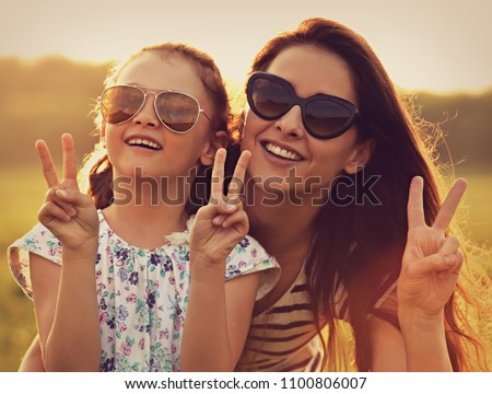 Fashion kid girl embracing her mother in trendy sunglasses and showing victory sign by hands nature background. Closeup toned portrait of happy life. #1100806007