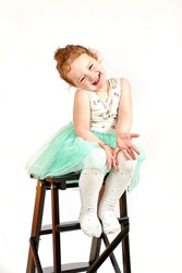 Fashion little girl in green dress, in catwalk model pose, stock photo.