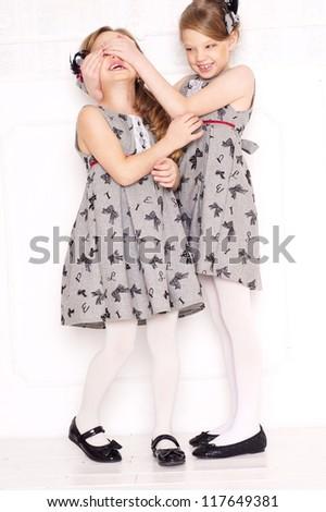 fashion little girls posing in gray dresses - stock photo