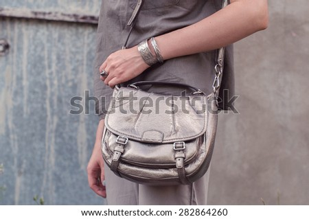 Fashion look background: minimalist outfit in beige and gray with metallic silver bag, grunge wall in the background