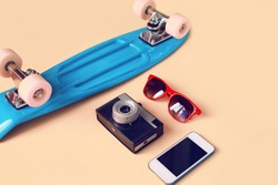 Fashion look concept. Blue skateboard, red sunglasses, vintage camera and screen smartphone. Trendy colorful photo