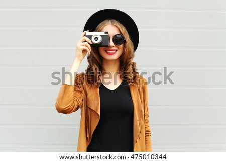 Fashion look, pretty cool young woman model with retro film camera wearing a elegant hat, brown jacket, curly hair outdoors over city grey background
