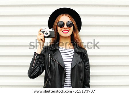 Fashion look, pretty young woman model with retro film camera wearing elegant black hat, leather rock jacket over white background
