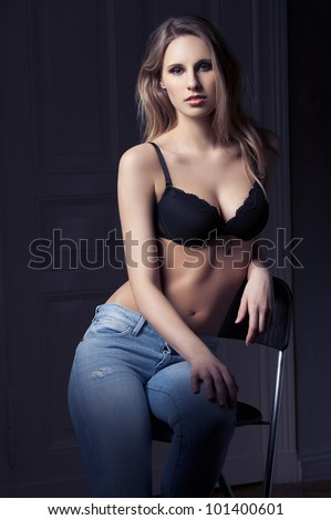 fashion low key shot of beautiful hot blond lady in black bra lingerie and jeans on dark indoor backgound