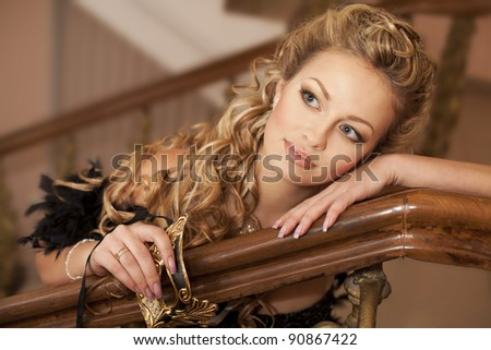 Fashion luxury retro portrait of beautiful sexy young woman with venice golden mask in the theater hall classic Interior art girl blond hair closeup