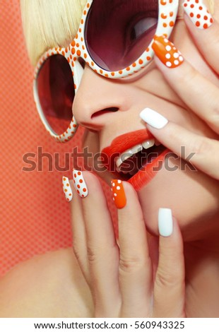 Fashion makeup and manicure orange color with a design of dots on the nails of the girl the blonde in glasses. #560943325
