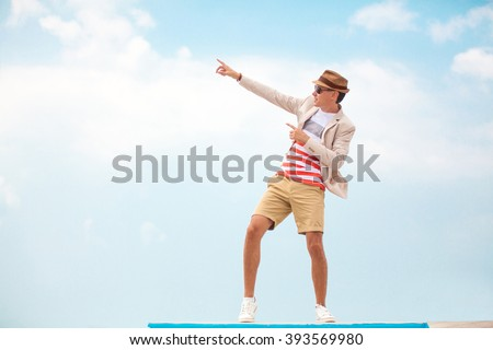 fashion man in hat and glasses pointing on copy space