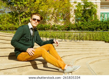Fashion man in sunglasses, jacket and jeans is sitting on stairs