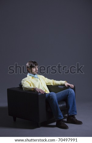 fashion man in yellow shirt sitting in leather chair