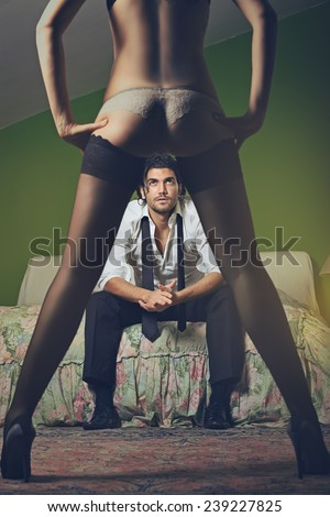 Fashion man looks at woman with sensual legs . Seduction and passion concept